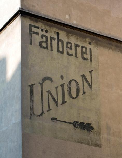 Wundervolle Schriftmischung am Frankfurter Platz. Witzig und typografisch unsinng sind der Schwung am U und der Punkt über über dem Großbuchstaben-I.